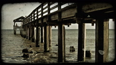 Waves hit ocean pier. Vintage stylized video clip. Stock Footage