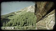 Old log cabin and mountain. Vintage stylized video clip. Stock Footage