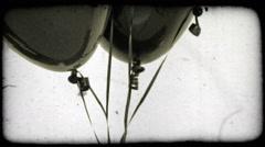 Tilt shot of a cluster of black balloons. Vintage stylized video clip. Arkistovideo