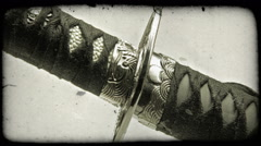 Close-up shot of a katana sword being pulled out of its sheath. Vintage stylized Stock Footage
