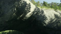 Shadows of the pines are moving quickly in a cave with huge holes-timelapse Stock Footage