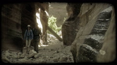 Couple hikes through canyon. Vintage stylized video clip. Stock Footage