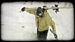 Skier carries skis up powdery hill. Vintage stylized video clip. Stock Footage
