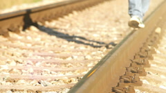 A footage of a teenager strutting along the railway in sneakers Stock Footage