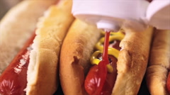 Grilled hot dogs on a white hot dog buns with mustard and ketchup. - stock footage