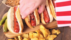 Grilled hot dogs on a white hot dog buns with chips and baked beans on the side. Stock Footage