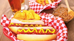 Grilled hot dogs with mustard and ketchup on the table with draft beer. - stock footage