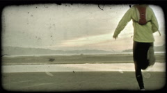 Couple jog along desert ground. Vintage stylized video clip. Stock Footage