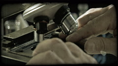 Man positions plate and looks into microscope. Vintage stylized video clip. Stock Footage