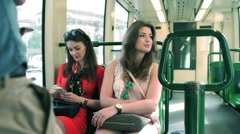 Girlfriends riding by the tram and using smartphone, steadycam shot Stock Footage