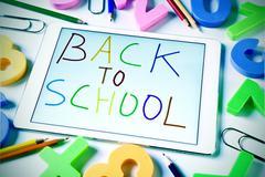 Sentence back to school handwritten in a tablet, slight vignette added Stock Photos