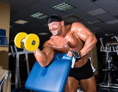 Handsome athletic man bodybuilder doing exercises with dumbbell in gym Stock Photos