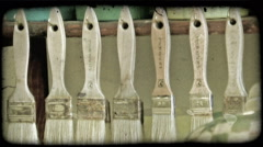 Panning shot of paintbrushes hanging from a shelf. Vintage stylized video clip. Stock Footage