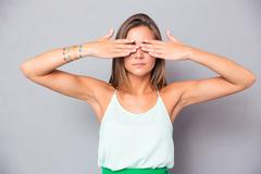 Girl covering her eyes with hands - stock photo