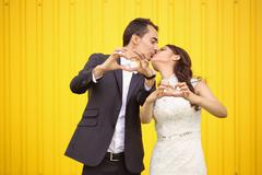 Bride and Groom doing love sign with their hands - stock photo