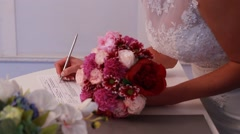Bride puts signature at marriage - stock footage