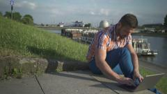 Man writing on a laptop on the stairs by the river, pan shot, right Stock Footage