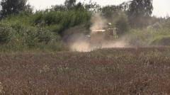 Harvester causes dust on thrashing grain field Stock Footage
