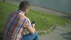 Man browsing smartphone, sitting on stairs by the river Stock Footage
