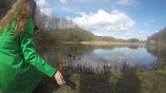Girl with green coat feed mallard duck birds near lake. 4K Stock Footage