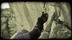 Man Scales Cliff. Vintage stylized video clip. Stock Footage