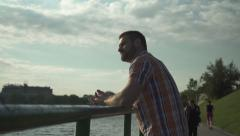 Pensive man standing near the river Stock Footage