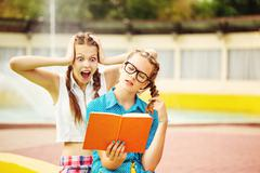 Best friends emotionally discussing the book in park. - stock photo