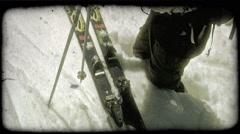 Skier puts on skis on mountain peak. Vintage stylized video clip. Stock Footage
