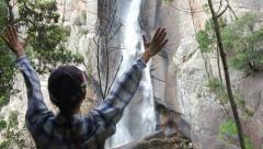 Young woman open arms to waterfall, Piscia di Ghjaddu, Corsica HD Stock Footage