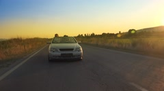 Couple driving convertible, cabriolet car with sunset sky. Steadicam shot.. U Stock Footage