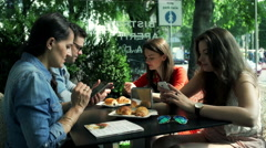 Friends sitting in the cafe and using mobile phones, steadycam shot Stock Footage