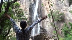 Young woman open arms to waterfall, Piscia di Ghjaddu, Corsica HD - stock footage