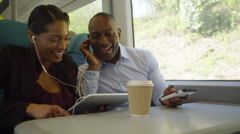 4K Attractive couple on train journey, using technology to pass the time Stock Footage