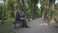 Businessman working on laptop, sitting on bench in park. Stock Footage