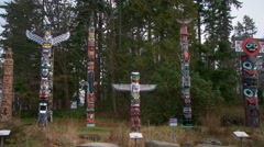 Seven First Nations totem poles in an outdoor display Stock Footage