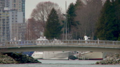Medium shot of bridge blocking entrance to Vancouver harbor filled with boats Stock Footage