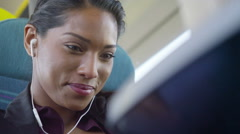 4k Beautiful woman on train journey relaxing with earphones and computer tablet Stock Footage