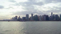 Panning long shot of Vancouver skyline from across water Stock Footage