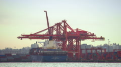 Long shot of huge cranes loading cargo on an ocean barge Stock Footage