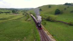 Aerial tracking shot of steam train in English countryside Arkistovideo
