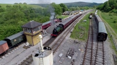 Aerial tracking shot of Steam train leaving Bolton Abbey Station Stock Footage