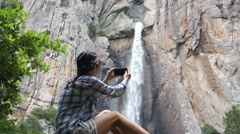 Young woman uses a smartphone to video a beautiful view HD - stock footage