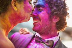 Bride and groom in the city with holi powder - stock photo