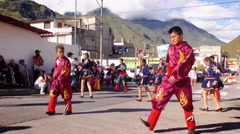 Dancers in colorful traditional costumes dancing on the streets of Banos for Stock Footage