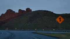 Stock Video Footage of POV-Driving I-70 in the Utah desert as evening falls last sun hits cliff