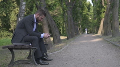 Busienessman browsing the smartphone sitting on wooden bench in park. Stock Footage