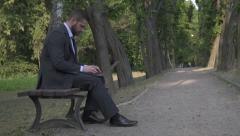 Businessman working on laptop, sitting on bench in park, pan and tilt shot. Stock Footage