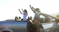 Young hipster having fun dancing in convertible cabriolet car. UHD 4K stock  Stock Footage