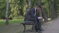 Busienessman browsing the smartphone sitting on wooden bench in park, pan shot. Stock Footage