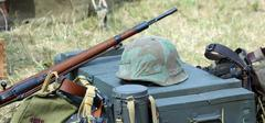 helmet of soldier uniform with a rifle in the army camp - stock photo